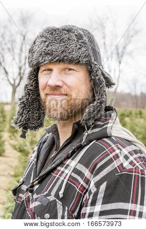 Rugged outdoorsman in fur hat with ear flaps outside in winter smiling