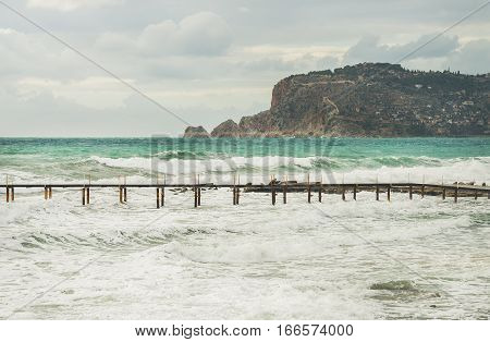 Stormy Mediterranean sea in winter in Alanya, Turlkey. View over Alanya castle hill, waves and pier