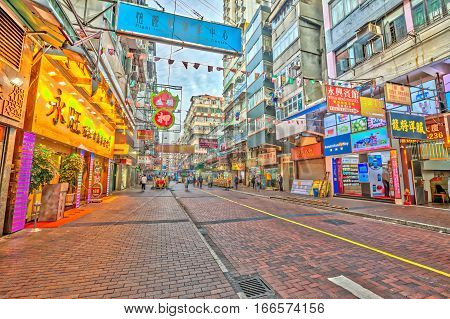 Hong Kong, China - December 5, 2016: Temple Street near Nathan Road, Yau Ma Tei, Kowloon, at twilight. Temple Street Night Market is a popular street bazaar and famous tourist attraction in Hong Kong.