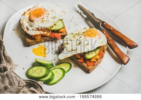 Breakfast toasts with vegetables and fried egg on white plate over grey marble background, selective focus, horizontal composition. Healthy, clean eating, dieting food concept
