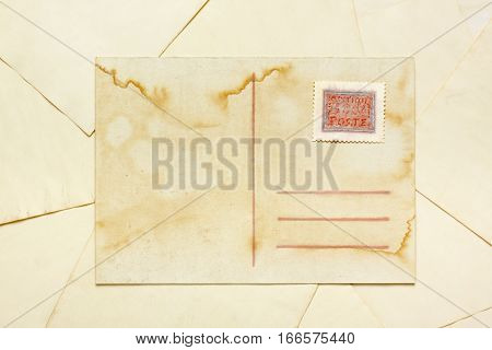 Aged empty postcard with painted abstract postage stamp over aged paper sheets
