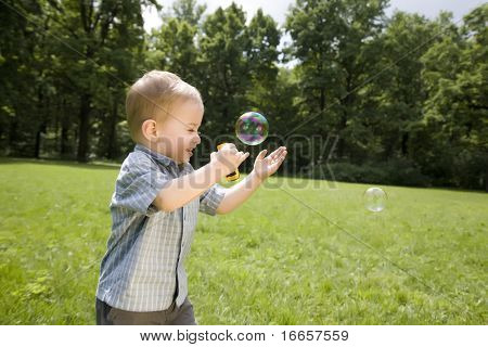Little Boy Catch Soap Bubbles On The Green Grass