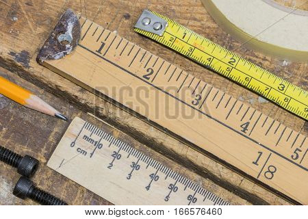 Old yard stick rulers and tape measures on worn workshop table with pencil tape and bolts
