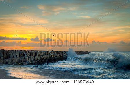 Sunrise at ocean jetty seascape shoreline waves