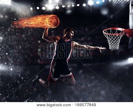 Player throws the fireball in the basket in the stadium full of spectators