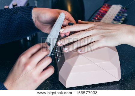 The manicurist holds hands of the client in beauty salon on desktop for manicure with nail polishes, napkins, creams and lighting instruments
