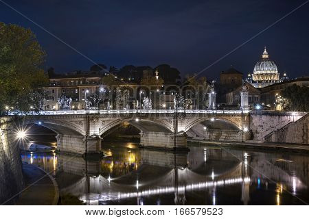 Saint Peter cathedral over Tiber river in Rome Italy at night. Bridge Vittorio Emanuele II.