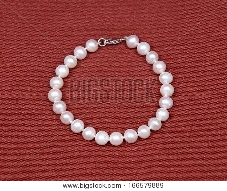 Freshwater white pearl necklace on red fabric background