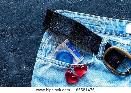 concept male contraception condom in jeans pocket top view.