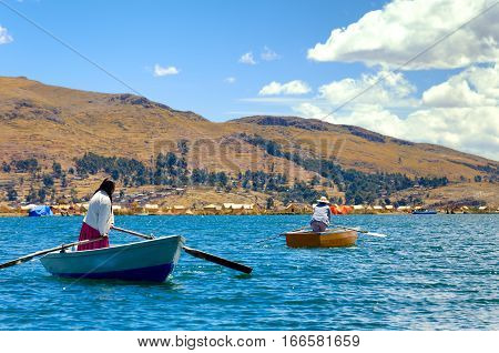 UROS FLOATING ISLANDS PERU - SEPTEMBER 19: Women in boats in the Uros Floating Islands Peru on September 19 2014