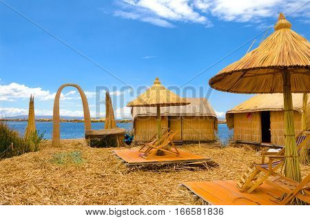 Umbrellas and buildings on one of the Uros Floating Islands on Lake Titicaca in Peru