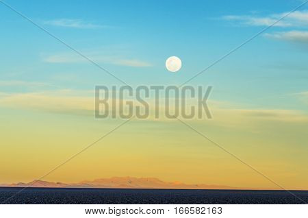 Moon brightly visible over the salt flats of Uyuni Bolivia