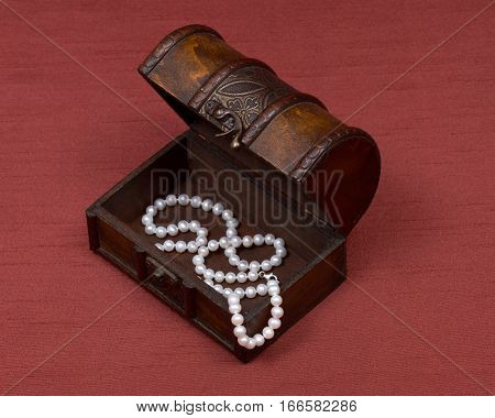 Wooden vintage jewelry box with freshwater white pearls necklace on red fabric background