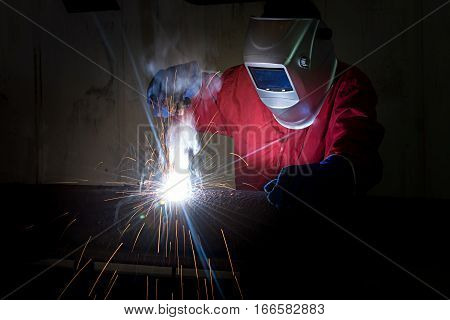 welder at work with sparks fire in the industry