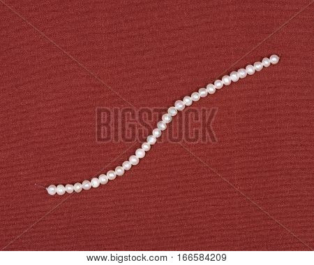 String of beautiful shiny small freshwater white pearl beads on red fabric background