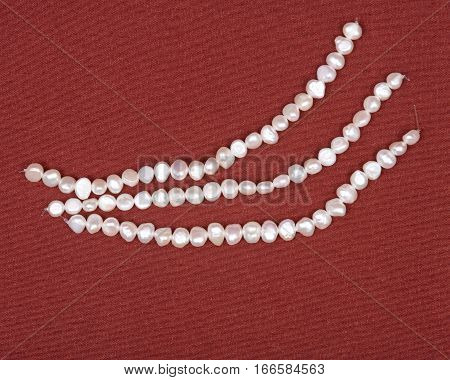 Strings of natural white freshwater pearl beads on red fabric background