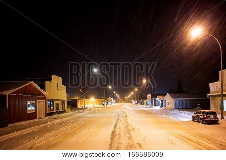 A long line of snow plowed down the centre of small town main street lined by street lights and stores at night under a snowfall