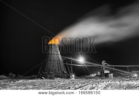 A large coned industrial wood chip burner with a fire inside shooting sparks out to the top in orange selective color at a sawmill yardsite in black and white at night in winter