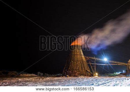 A large coned industrial wood chip burner with a fire inside shooting sparks out to the top in a sawmill yardsite at night in winter