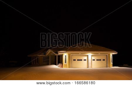 A vacant modern yellow stucco house lit up by lights under the eaves at night surrounded by deep untouched snow in winter