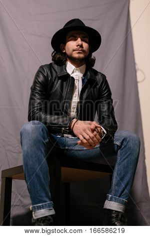 sedentary portrait of young trendy guy in a hat and leather jacket