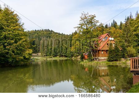 House near the lake in the forest autumn day.