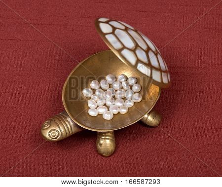 Decorative turtle jewelry box and freshwater white beads of pearl on red fabric backboard