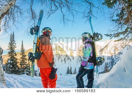 Freerider man and woman is standing on the mountainside in a helmet and with a backpack and looks into the distance