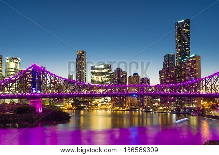 View of illuminated bridge and skyscrapers with reflection in Brisbane at twilight