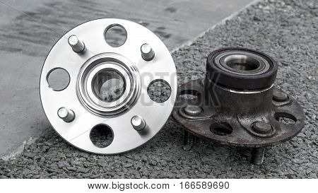 Car Suspension and car bearing parts concept - New and old rear wheels car bearing on asphalt floor in garage and copyspace