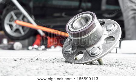 Car Suspension and car bearing parts concept - New rear wheels car bearing on asphalt floor in garage and copyspace