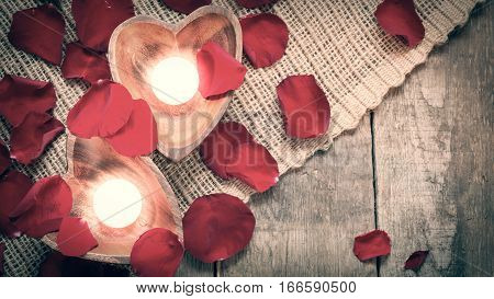Two Enlightened Candles In Heart-shaped Candleholders With Rose Petals