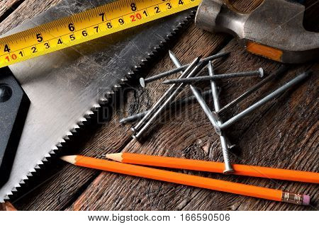 A close up image of an old hammer, saw blade, tape measure, and pencil.