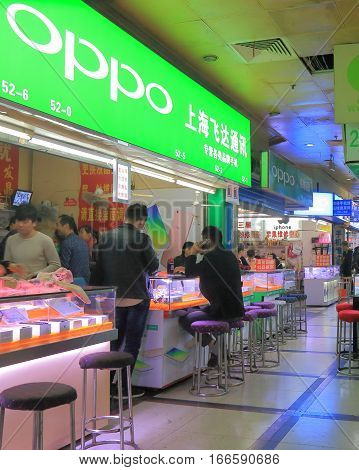 SHANGHAI CHINA - OCTOBER 31, 2016: Unidentified people shop at OPPO mobile phone shop Bu Ye Cheng Commercial market. OPPO is Electronics Corp is a Chinese electronics manufacturer based in Guangdong.