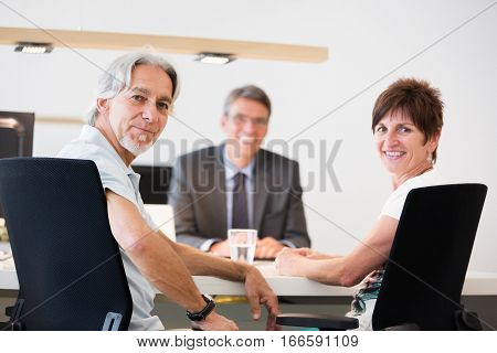 a retired couple is talking to their financial advisor