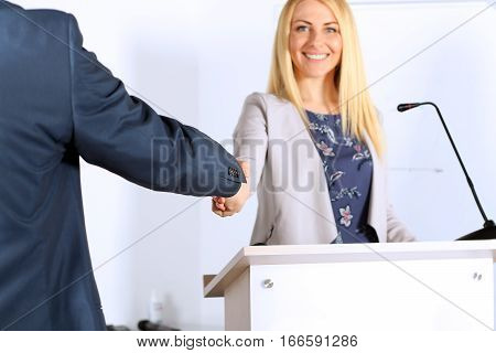 A firm handshake between beautiful businesswoman and man at the presentation