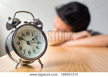 Man sleeping on wood table with alarm clock