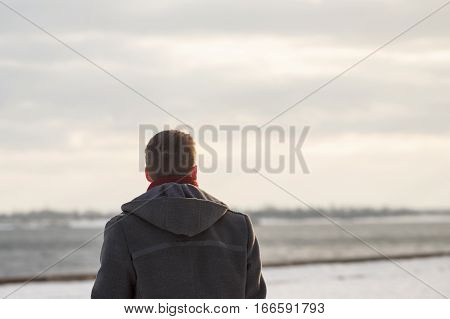 Lonely man in a coat and scarf in winter park. He looks up at the sky and the river. Man is unrecognizable.