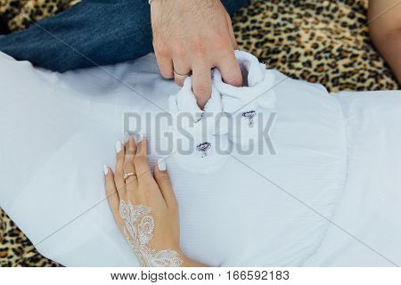 Pregnant Woman And Father Holding White Baby Shoes