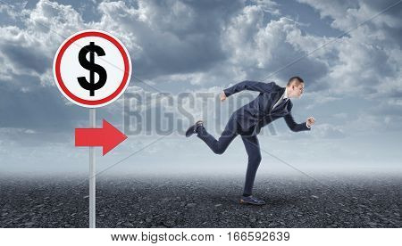 Businessman running on the asphalt and road sign with the dollar sign. Business development. Make profits. Rise in profitability.