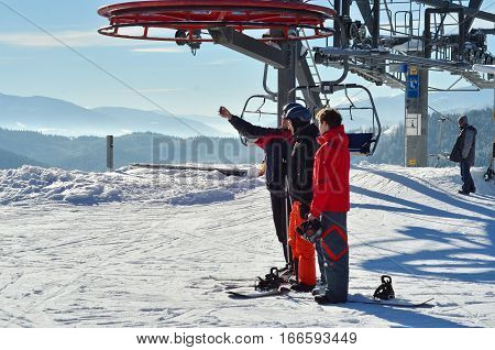 BUKOVEL, UKRAINE - December 2, 2016: Skiers taking pictures on top of mountain on ski slope. Bukovel is the most popular ski resort in Ukraine.