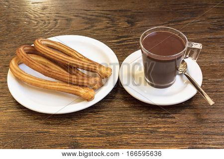 Churros, traditional Spanish, especially Madrid, dessert, often for Sunday breakfast, with a cup of chocolate on a wooden board texture, retro style, with copyspace