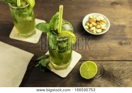 A photo of a mojito cocktail with mint leaves, a wedge of lime, and a drinking straw, on a dark wooden background with copy space. Selective focus