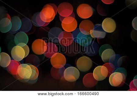 A multitude of circular multicolored dots on a dark black background bokeh effect