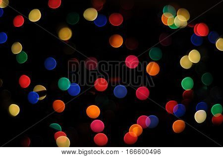 Bokeh Effect multicolored round circular dots of red, orange, yellow, green, blue rainbow colors with dark black background