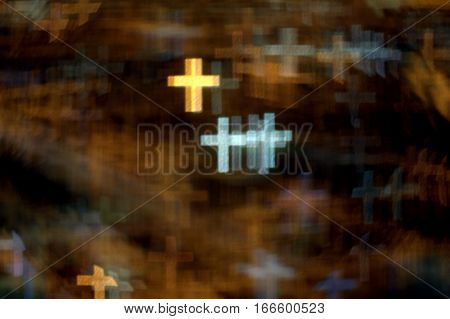 numerous golden and white crosses on a dark golden background of multiple crosses bokeh effect