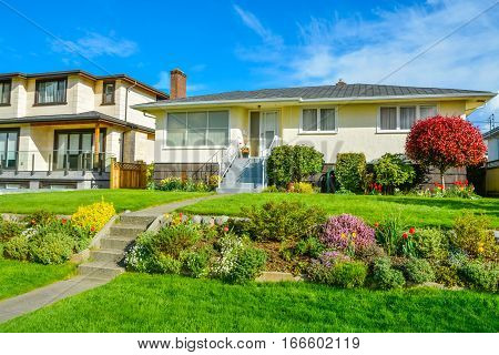 Average family residential house with landscaped front yard on blue sky background