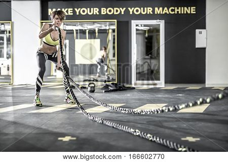 Active girl with parted lips does exercise with the fitness ropes in the gym. She wears multi-colored sneakers, black pants with white strips, lime top. Shoot from the side. Horizontal.