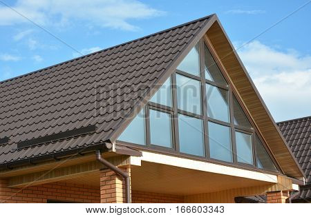 Modern house attic with metal roofing panoramic window skylight roof window and rain gutter system. Attic Skylight.