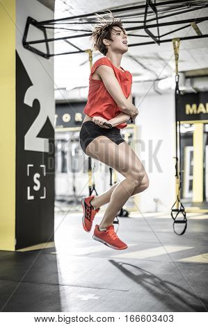 Glad girl jumps with a skipping rope in the gym on the background of the hanging TRX straps. She wears black shorts, red sleeveless and sneakers. Her hair is flying in the air. Vertical.